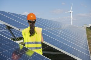 A female engineer is standing beside the solar panel