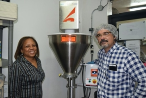 Rodríguez poses with Exporting Quality staff member, Raquel Travieso, next to the new cacao powder filler.